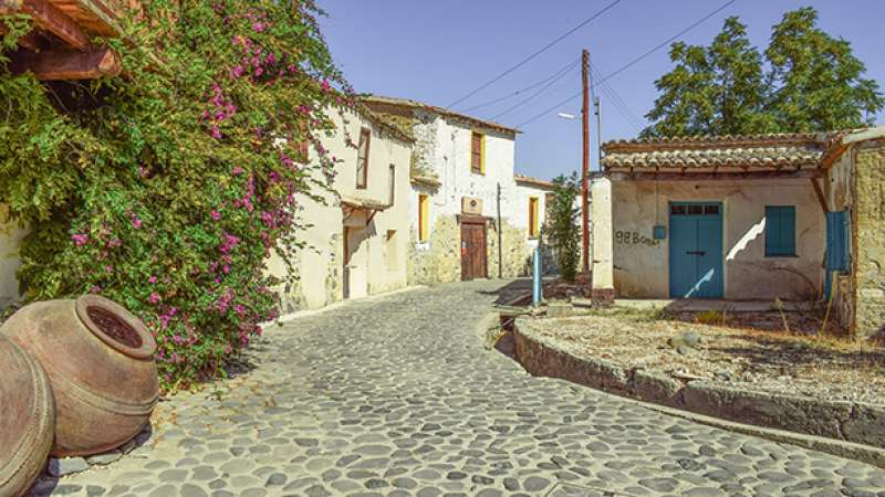 Little street with flowers, houses and clay vase